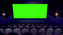 Dark empty cinema hall with green screen.
