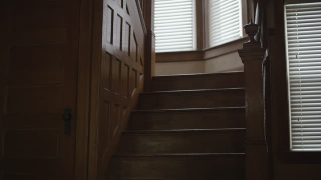 Dark, empty, scary, interior shot featuring the foray, creepy oak staircase and wainscoting in an old home. Camera dollies forward.