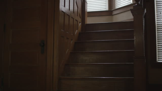 vídeos de stock e filmes b-roll de dark, empty, scary, interior shot featuring the foray, creepy oak staircase and wainscoting in an old home. camera dollies forward. - escadaria