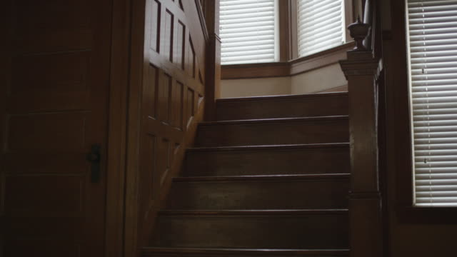 vídeos de stock, filmes e b-roll de dark, empty, scary, interior shot featuring the foray, creepy oak staircase and wainscoting in an old home. camera dollies forward. - escada objeto manufaturado