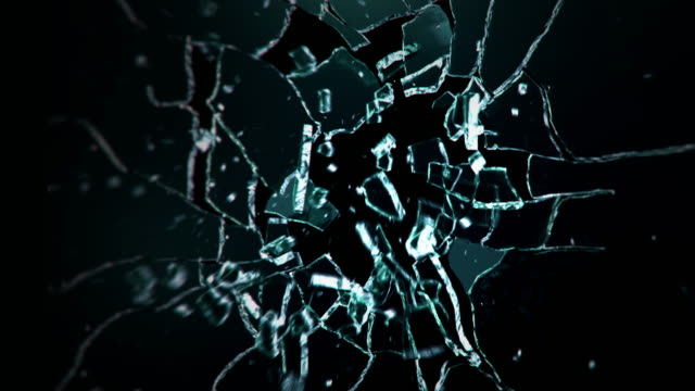 dark glass wall explosion. bullet exploding a glass pane - sparare video stock e b–roll