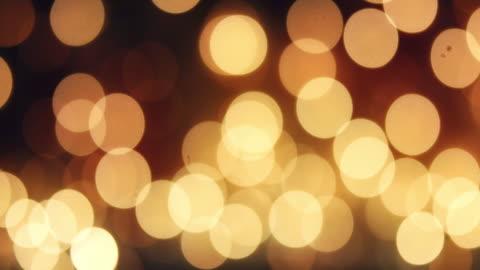 dunkles gold reflexionen und bokeh - unscharf gestellt reichen lichtleck effekt - fairy lights stock-videos und b-roll-filmmaterial