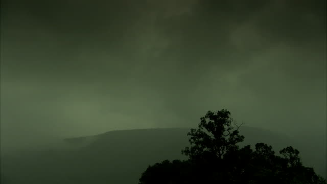 Dark gray clouds drift over a mountain in Chennai, India. Available in HD