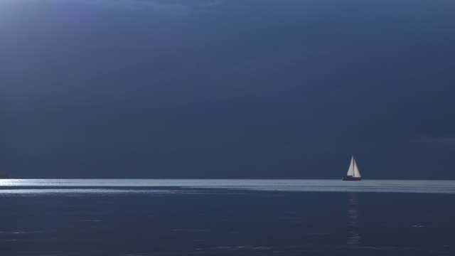 dark moody sky over a sailboat in calm waters - sailing boat stock videos & royalty-free footage