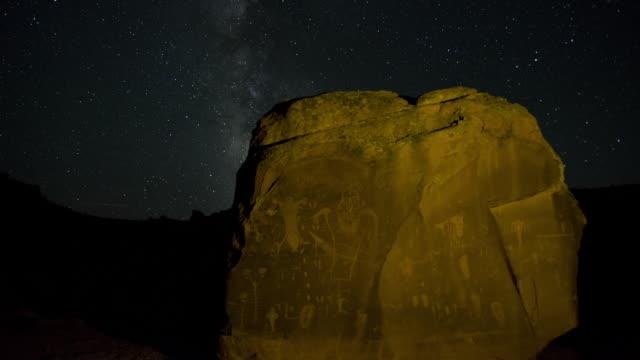 vidéos et rushes de a dark night sky surrounds a native american petroglyphs. - utah