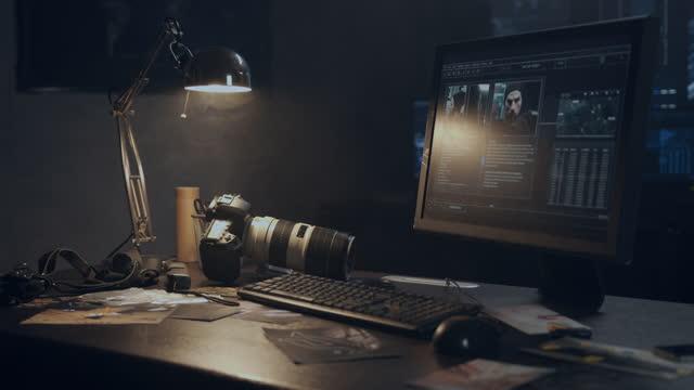 vídeos y material grabado en eventos de stock de una oficina oscura de una agencia de detectives privada, encendida comprar la luz débil de una lámpara y varios monitores - detective