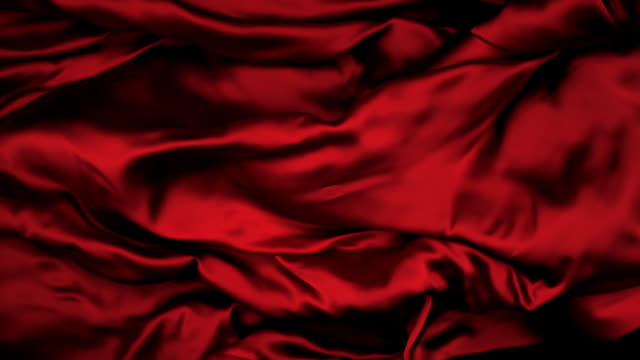 vidéos et rushes de dark red silky fabric flowing and waving horizontally in super slow motion and close up, black background - red