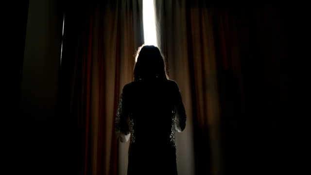 dark room.woman opening curtains and looking out - curtain stock videos & royalty-free footage