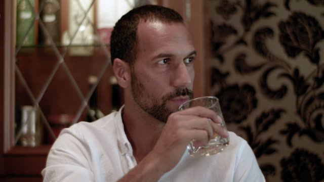 vídeos de stock e filmes b-roll de dark short haired tanned man with trimmed beard in white shirt in his mid 30s sitting in a cigar lounge with a glass of bourbon whiskey - he grabs the glass and takes a sip of his alcoholic drink - table top shot