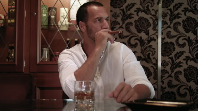 dark short haired tanned man with trimmed beard in white shirt in his 30s sits in a cigar lounge with a glass of scotch whiskey - he smokes and grabs the glass and takes a sip of his alcoholic drink - ashtray with cigar out of focus in foreground