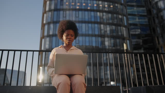 a dark skinned young female entrepreneur types an email on her laptop against the business center - low angle view stock videos & royalty-free footage
