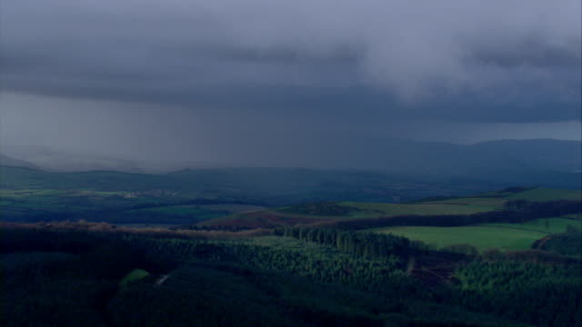 dark storm clouds loom above the countryside. available in hd. - rain stock videos & royalty-free footage