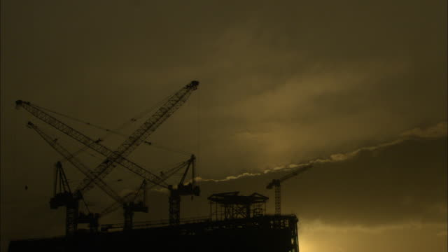 ws la dark sunset clouds behind multiple cranes sitting atop building under construction, guilin, guangxi zhuang autonomous region, china - guangxi zhuang autonomous region china stock videos & royalty-free footage
