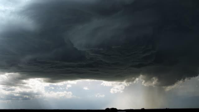 Dark supercell cloud unloading rain or hail over a prairie landscape