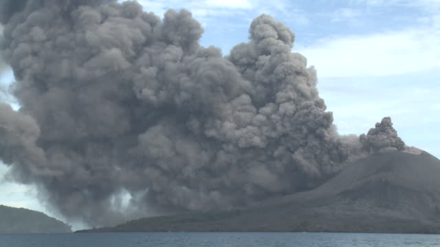 dark thick ash pours from volcano and flows down flanks into ocean, krakatoa, indonesia, november 2010 - sprengkörper stock-videos und b-roll-filmmaterial
