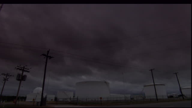 dark, threatening clouds hang over rural buildings as traffic speeds by. - storage tank stock videos and b-roll footage
