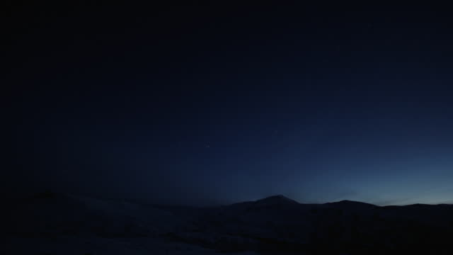 dark to dawn over snowy mounains timelapse - artbeats stock videos & royalty-free footage