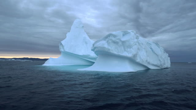 dark waves lap at a picturesque white iceberg at sunset on disko bay - 氷山点の映像素材/bロール