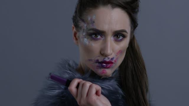 dark-haired fashion model in silver fox fur holds violet lipstick. fashion video. - organismo vivente video stock e b–roll