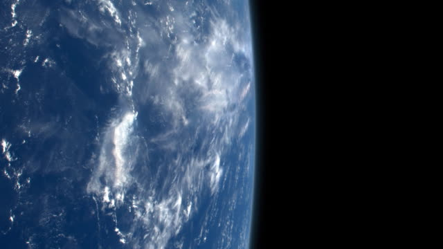 Darkness of space with blue Earth under a layer of clouds