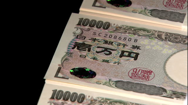 Darkness surrounds bundles of ten thousand yen bills in Tokyo, Japan.