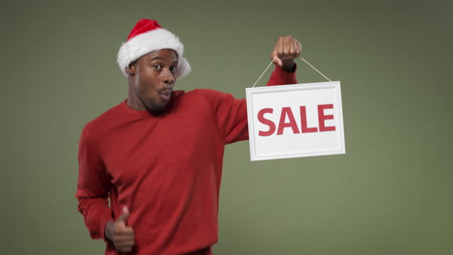 """stockvideo's en b-roll-footage met een donker-gevilde mens in een heldere rode sweater en de hoed van kerstmis houdt een """"verkoop"""" teken en glimlacht - kerstversiering"""