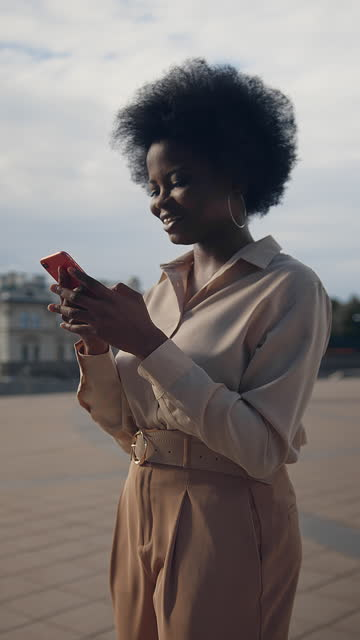 a dark-skinned pretty female entrepreneur  in a beige outfit is texting  on her red smartphone with a smile, passing by a modern skyscraper - hairstyle stock videos & royalty-free footage