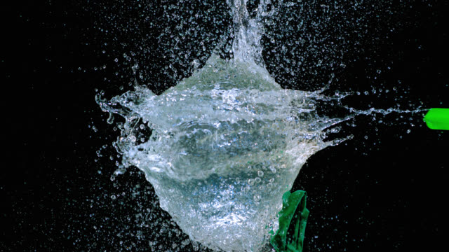 SLO MO of dart puncturing a green water balloon