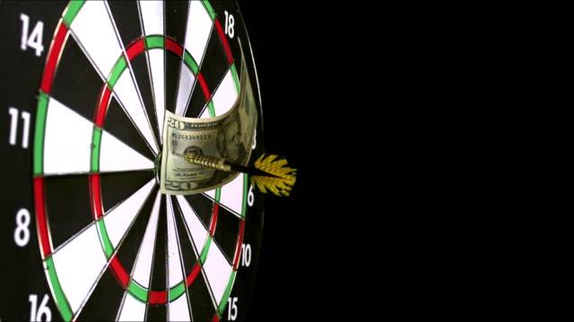 """dart with 20 dollars bill hitting dartboard against black background, slow motion"" - twenty us dollar note stock videos & royalty-free footage"