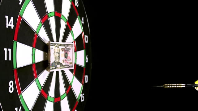 """""""dart with 50 dollars bill hitting dartboard against black background, slow motion"""" - dart stock videos & royalty-free footage"""