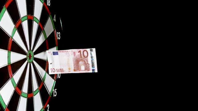 stockvideo's en b-roll-footage met dart with money hitting dartboard against black background, slow motion - tien euro