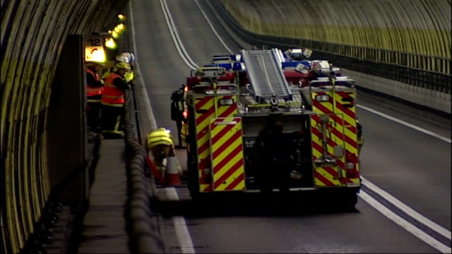 vídeos de stock e filmes b-roll de dartford tunnel major emergency rehearsal; fire engines along and past as pull up in tunnel, firefighters jump out / fire officers in protective... - major road