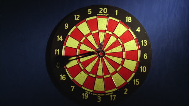 ms darts hit target in bull's eye at dart board on blue wall - bull's eye stock videos and b-roll footage
