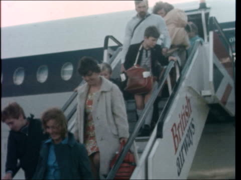 darwin cyclone refugees; england: london: heathrow airport: woman and kids off plane, down steps, towards: kid. l-r: women and children off plane -... - vortex stock videos & royalty-free footage