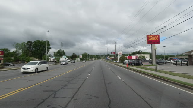 dashboard camera point of view of commercial signs along a town road with less traffic amid the 2020 global coronavirus pandemic in north georgia, usa - gulf coast states stock-videos und b-roll-filmmaterial