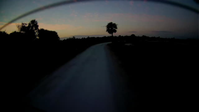 Dashboard camera point of view of dirt road driving at twilight