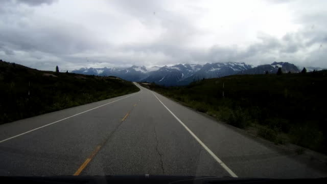 vídeos de stock e filmes b-roll de dashboard camera point of view of driving in a cloudy day in canada with snowcapped mountain in distant. - alfalto