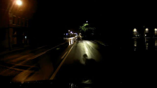 dashboard camera point of view of driving in a rainy night with no traffic in america amid the coronavirus pandemic which declared social distancing and stay at home order. - 追跡点の映像素材/bロール