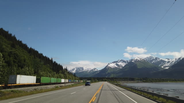 stockvideo's en b-roll-footage met dashboard camera point of view of driving in alaska while freight train runs next to the highway in sunny day - alaska verenigde staten