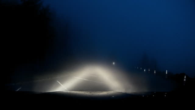 Dashboard camera point of view of driving in the parking lot under heavy fog at night