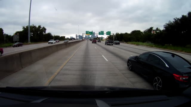 dashboard camera point of view of driving on highway approaching downtown houston area, texas - フロントガラス点の映像素材/bロール