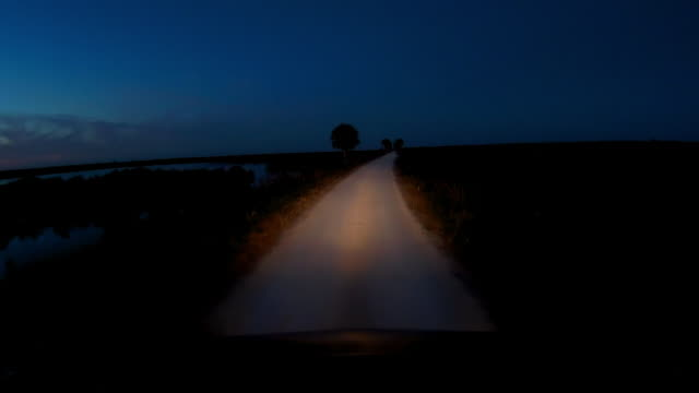 vidéos et rushes de dashboard camera point of view of driving on rural dirt road at twilight - route à une voie
