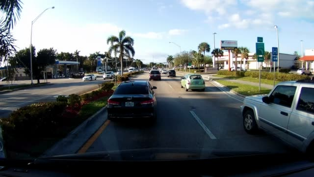 Dashboard camera point of view of driving passing Chevron gas station and Walgreens in Miami