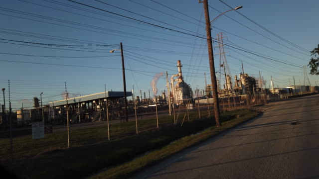 dashboard camera point of view of driving passing exxon mobil plant at sunset in texas - exxon stock videos & royalty-free footage