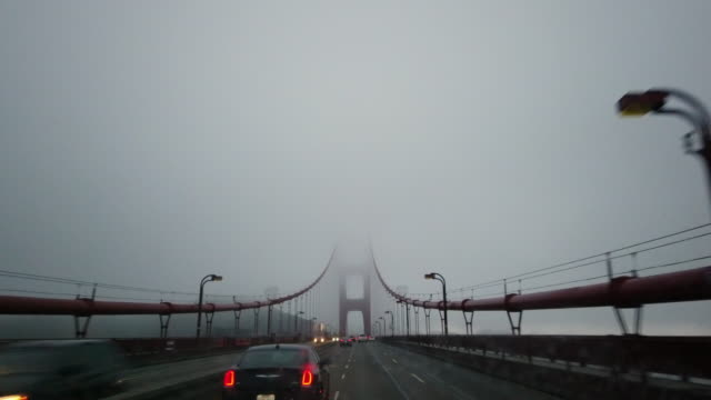 stockvideo's en b-roll-footage met dashboard camera point of view of driving through golden gate bridge in a foggy day - hangbrug