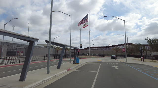 dashboard camera point of view of driving to the border fence and people wearing face mask walking on the sidewalk. - arrow symbol stock videos & royalty-free footage