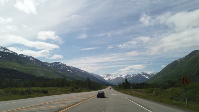dashboard camera point of view of driving towards snowcapped mountains in alaska - recreational pursuit stock videos & royalty-free footage