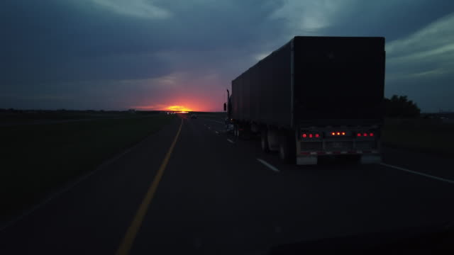 dashboard camera point of view of highway driving at sunset - articulated lorry stock videos & royalty-free footage