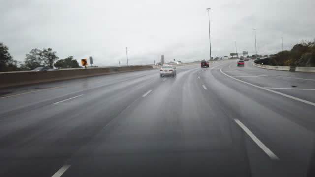 dashboard camera point of view of highway driving in a rainy day - winding road stock videos & royalty-free footage