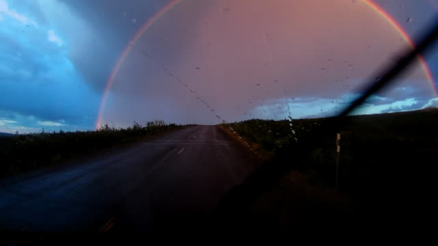stockvideo's en b-roll-footage met dashboard camera point of view of rainbow and driving at sunset on alaska dalton highway after rainstorm - schemering